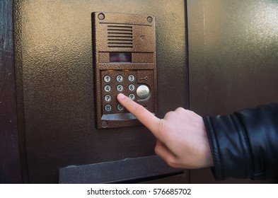 The hand presses the button on the intercom