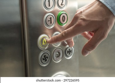 Hand pressing the alarm button in the elevator
