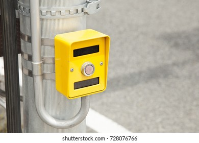 Hand pressing a button at traffic lights on pedestrian crossing.