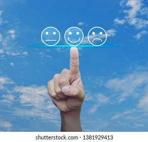 Hand pressing excellent smiley face rating icon over blue sky with white clouds, Business customer service evaluation and feedback rating concept