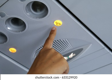 Hand pressing flight attendant call button