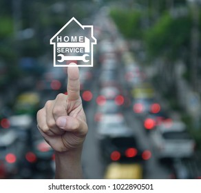 Hand pressing hammer and wrench with house icon over blur of rush hour with cars and road, Home service concept