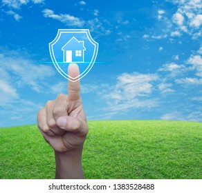 Hand pressing house with shield flat icon over green grass field with blue sky, Business home insurance and security concept