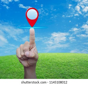 Hand pressing map pin point location button over green grass field with blue sky and white clouds, Map pointer navigation concept