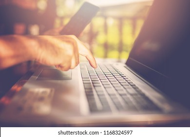 The hand is pressing on the notebook keyboard.