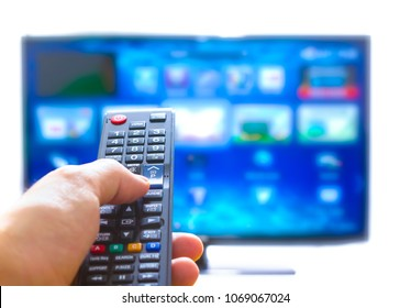 Hand pressing on remote control and changes channels thumb on the blue TV screen