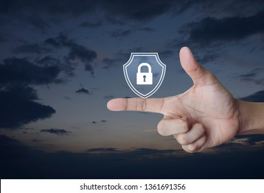 Hand pressing padlock with shield flat icon over sunset sky, Business security insurance concept