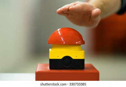 Hand pressing red emergency button