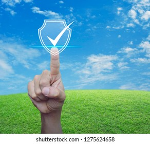 Hand pressing security shield with check mark icon over green grass field with blue sky, Internet cyber security and anti virus concept
