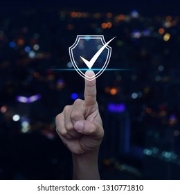 Hand pressing security shield with check mark icon over blur colorful night light city tower and skyscraper, Internet cyber security and anti virus concept