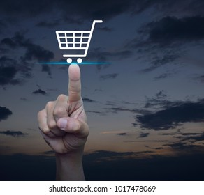 Hand pressing shop cart icon over sunset sky, Shopping online concept