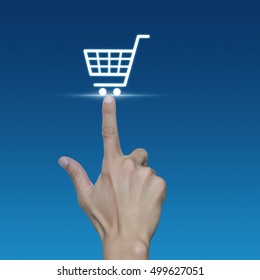Hand pressing shopping cart icon over blue background, Shopping online concept