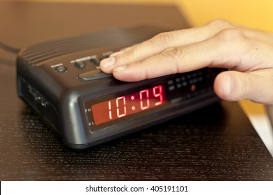 Hand pressing the snooze button on a digital alarm clock