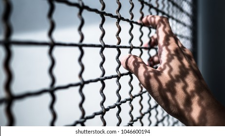 hand of prisoner holding rustic metal fence with pattern shadow, criminal locked in jail waiting for freedom