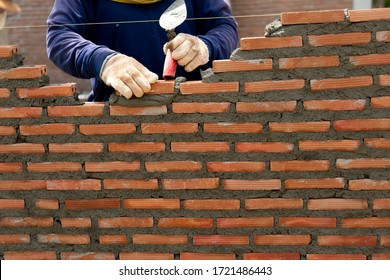hand of professional construction worker laying bricks In wall construction, construction and masonry concept