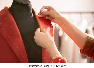 Hand of professional tailor using needle with white thread while sewing collar of red coat for one of clients