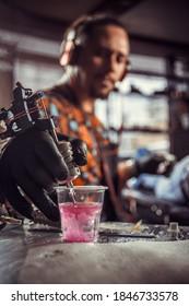 Hand des professionellen Tätowierers und einer Tätowierpistole.