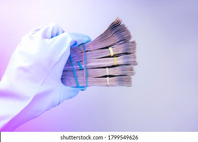 Hand projected with rubber glove holding, receiving or giving wad of European union Euro money cash banknotes, prevention virus spread, world money concept. Toned in modern  neon