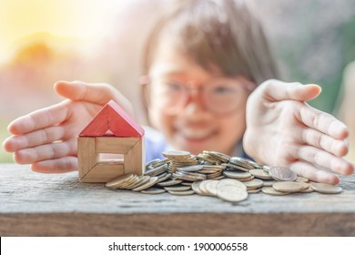 Hand protecting stacked coins and wooden house .Property investment and house mortgage financial concept,