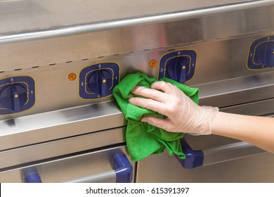 Hand in protective glove with rag cleaning kitchen equipment in the professional kitchen. Stainless steel surface. Early spring cleaning or regular clean up.