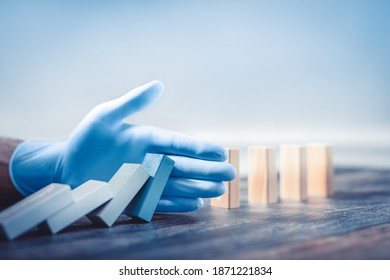 Hand with protective glove stopping domino effect.