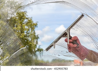 Hand in protective glove washing and cleaning window with professionally squeegee on background of cloudy sky. Summer windows cleaning. Maid cleans window.