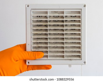 Hand in an protective rubber orange glove shows clogged air ventilation grille, cleaning service concept.