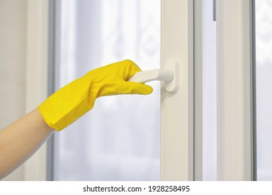 Hand in protective yellow rubber glove opens and closes PVC plastic window. Cleaning, maintenance and fixing.