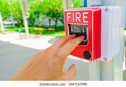 Hand pulling down the fire alarm button.