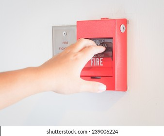 The hand  is pulling fire alarm on the wall