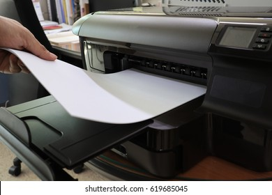 A hand pulling out the white paper from the printer
