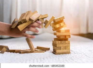 Hand of pulling out wood block fail on building tower at home and drape change, choice business risking dangerous project plan failure construction concept.