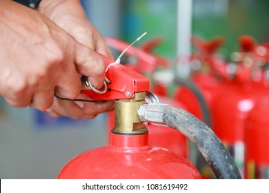 Hand pulling pin of fire extinguisher.