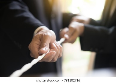 Hand pulling the rope, Grey background, cooperation concept as an element of the teamwork