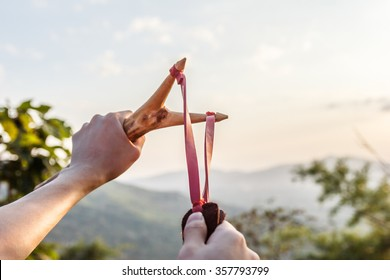 Hand pulling slingshot to shoot tree seed into forest under the mountain.