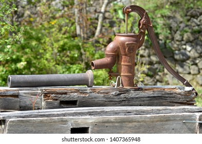 A hand pump used for water rests on top of a pile of wooden posts. It is rusted, with a water pipe near it. The posts were once used for a fence. Each post has a hole for a horizontal post.