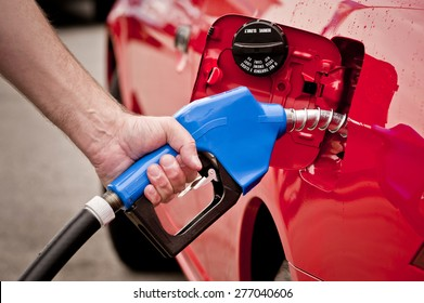 Hand Pumping Gas Into Red Car