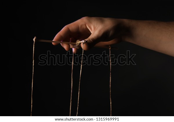 Hand of puppeteer on dark background