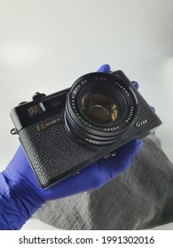 Hand with purple nitrile glove holds Yashica SLR camera. Old Japanese SLR manual focus camera manufacturer. Black vintage. Lense mount. Collectible. Malaysia. June 2021