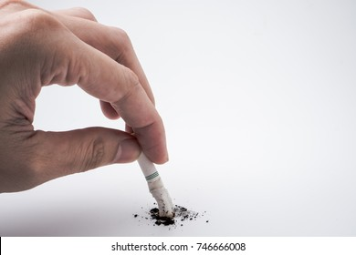 A hand push the cigarette stub on white background, Symbolic stop smoking concept, Free space for text