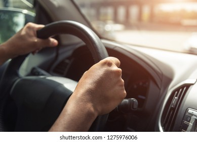 A hand pushes the cruise control button on a steering wheel