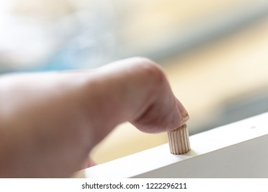 Hand pushes a wooden pen into the Board