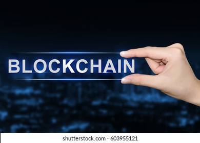 hand pushing blockchain button on blurred blue background