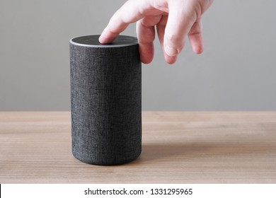 hand pushing button on smart speaker - turning or switching off microphone for privacy concerns