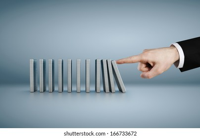 Hand pushing dominoes concept isolated on blue background