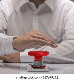 hand pushing emergency button, white shirt and reflexion. symbol of urgency and problem solving