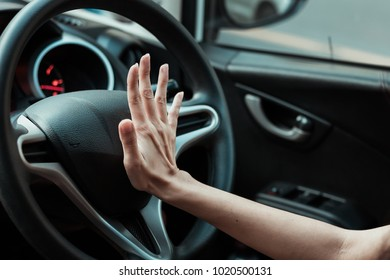 Hand pushing the horn button of the steering wheel inside the car with an anger.