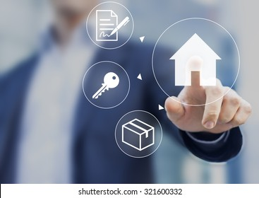 Hand pushing house button on screen with mortgage contract, keys and boxes symbols