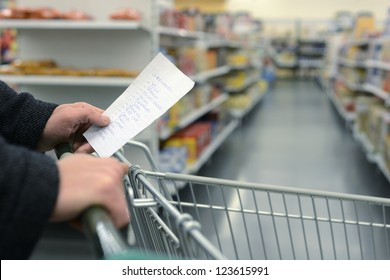 Hand pushing a shopping cart through the aisles of a supermarket, holding a list with groceries, with the daily necessities in handwriting on a slip of paper