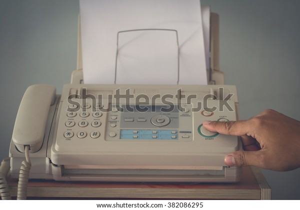 A hand pushing start button old fax retro style